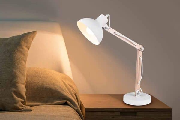 Cozy bedroom interior with book and reading lamp on bedside tabl